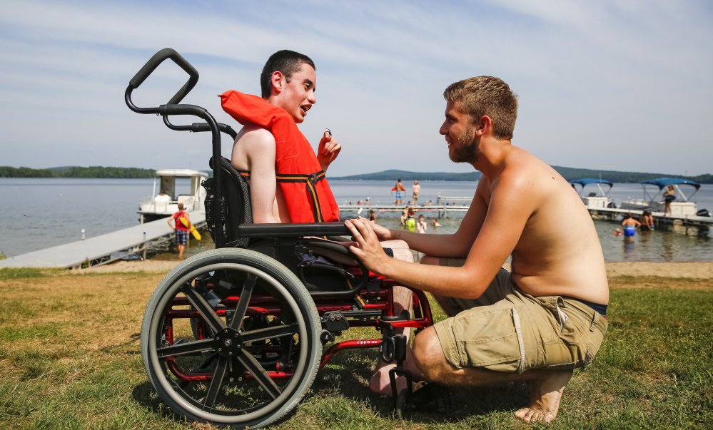 Andrew Artrip, left, and camp counselor Alex Schofield confer before they enter the water together at Pine Tree Camp in Rome. According to U.S. Census data, 16 percent of Maine residents – 206,000 people – have some physical disability, compared to 12 percent nationally.